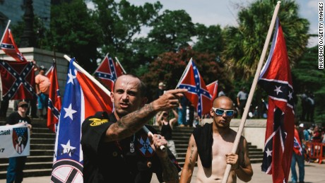 ( Left to Right ) A member of th Ku Klux Klan from Kentucky, USA and a member of the Loyal White Knights a branch of the Ku Klux Klan from Pelham, North Carolina are seen during a Klan rally at the South Carolina State House in protest against the removal of the Confederate Flag off of State House grounds July, 18, 2015. The rally came a little over a week after the removal of the flag which South Carolina's governor signed a law for the removal of the flag in the wake of the Charleston South Carolina church shooting in which nine African American's were killed. (Photo by Seth Herald/NurPhoto) (Photo by NurPhoto/NurPhoto via Getty Images)