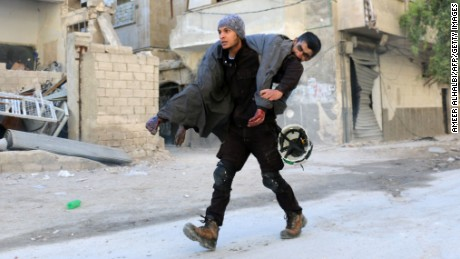 A Syrian civil defence volunteer, known as the White Helmets, carries an injured man on November 19, 2016 following a reported air strike on Aleppo's rebel-held neighbourhood of Bab al-Nayrab. Intense government air strikes and artillery fire killed at least 27 people in rebel-held parts of Syria's Aleppo, where hospitals have been destroyed and schools forced to close.