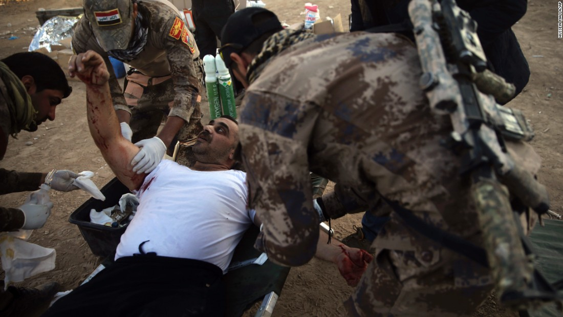 An Iraqi soldier treats a civilian injured by a mortar shell at a field hospital in Mosul on November 19.