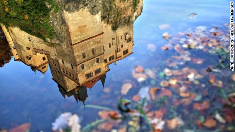 Kriebstein Castle is reflected in a puddle as the leaves on trees change to their Autumn colours in Kriebstein, eastern Germany on November 3, 2016. / AFP PHOTO / ZB AND dpa / Jan Woitas / Germany OUTJAN WOITAS/AFP/Getty Images