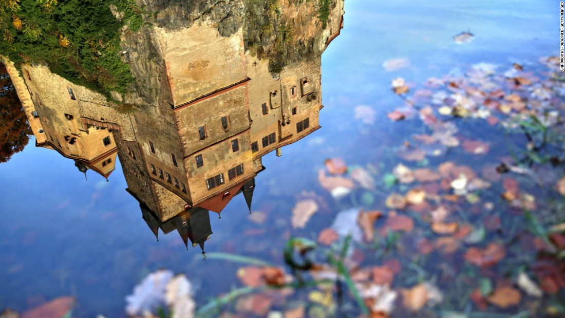 Kriebstein Castle -- one of Germany's most distinctive medieval fortresses -- is reflected in the still water of an autumn puddle.