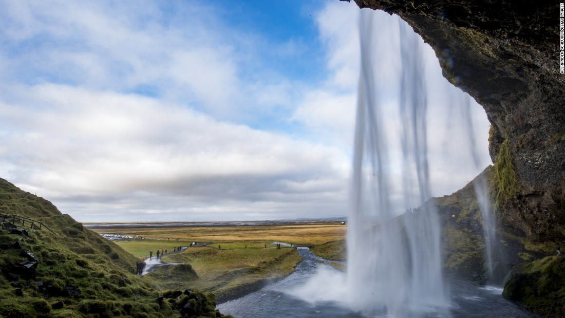 The waters of Seljalandsfoss Waterfall cascade over a cave mouth in Iceland. One of Iceland's premier attractions, the falls allow visitors to observe the Northern Lights through a screen of falling water.  <br />