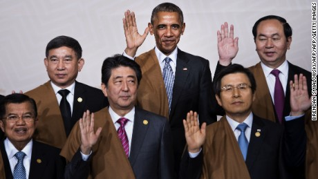 """(L to R back) Thailand's Deputy Prime Minister Prajin Juntong, US President Barack Obama and Vietnam's President Tran Dai Quang; (L to R front) Indonesia's Vice President Jusuf Kalla, Japan's Prime Minister Shinzo Abe and South Korea's Prime Minister Hwang Kyo-Ahn wave during the traditional """"family photo"""" on the final day of the Asia-Pacific Economic Cooperation (APEC) Summit at the Lima Convention Centre in Lima on November 20, 2016."""