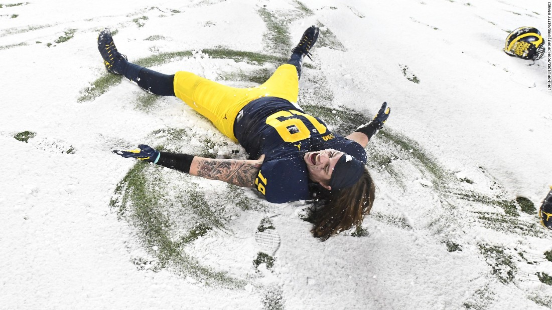 Michigan fullback Henry Poggi makes a snow angel after a 20-10 home win over Indiana on Saturday, November 19.