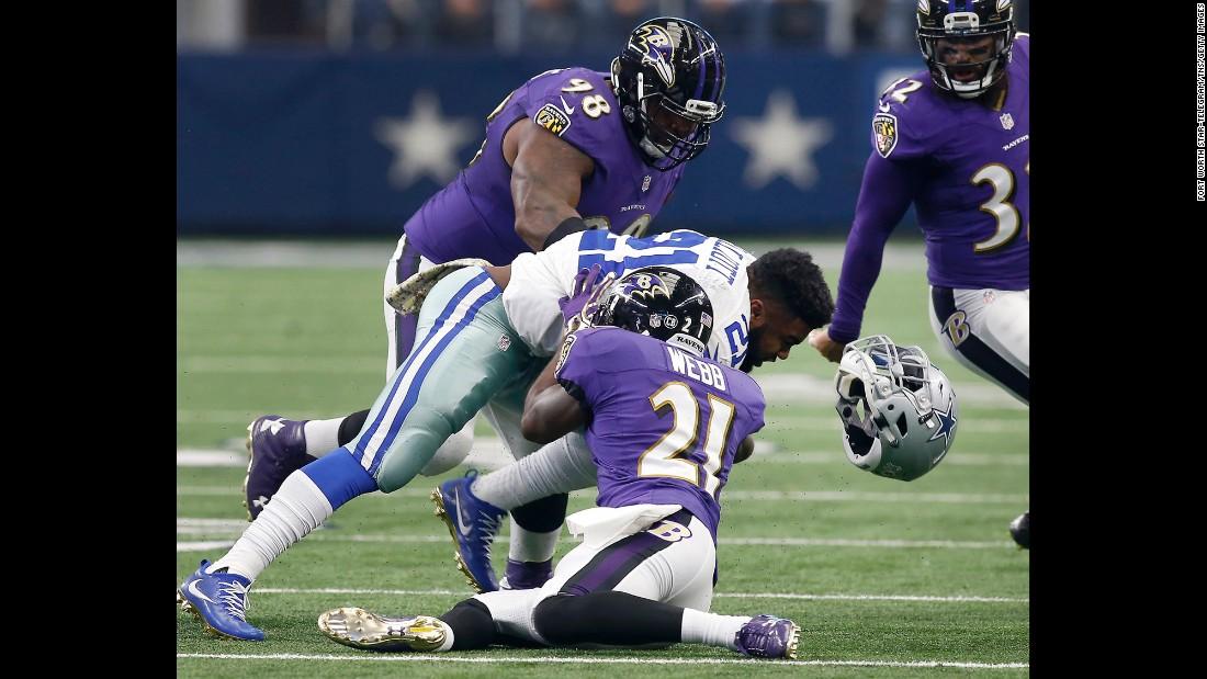 Dallas running back Ezekiel Elliott loses his helmet as he's hit by Baltimore safety Lardarius Webb on Sunday, November 20.