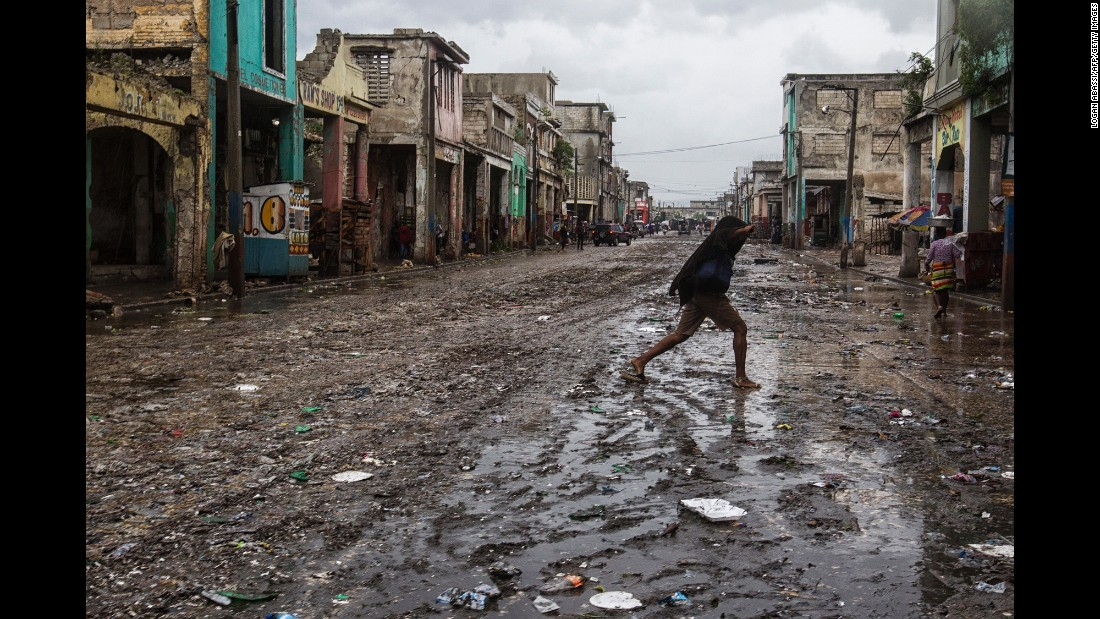 "A woman crosses a flood-affected street as Hurricane Matthew passes over Port-au-Prince, Haiti, on October 4. The storm <a href=""http://www.cnn.com/2016/10/08/americas/hurricane-matthew-death-toll-haiti/"" target=""_blank"">left behind widespread destruction across Haiti</a> and killed hundreds in its path."