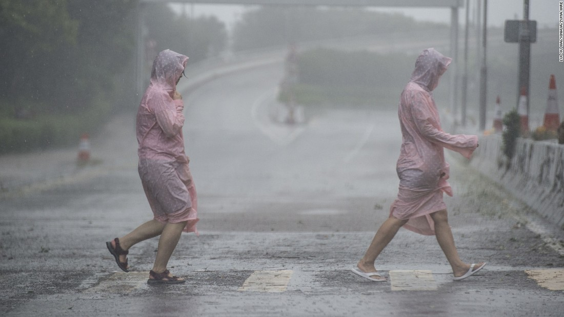 People walk on a Hong Kong street as Typhoon Haima hit the region on Friday, October 21.