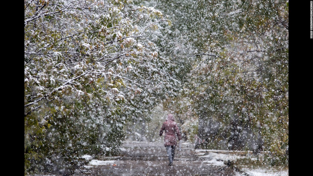 A woman walks in the snow in Omsk, Russia, on Tuesday, October 11.