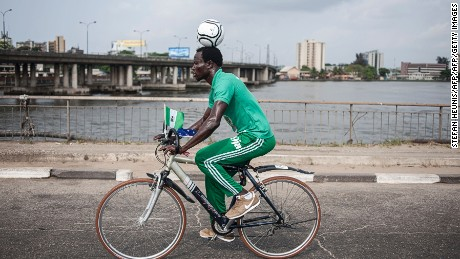 Harrison Chinedu balances a football on his head while riding a bicycle for a 103,6 km through the streets of Lagos on November 20, 2016.  Harrison Chinedu has set a new Guinness World Record for the greatest distanced travelled on a bicycle whilst balancing a football on the head. / AFP / STEFAN HEUNIS        (Photo credit should read STEFAN HEUNIS/AFP/Getty Images)