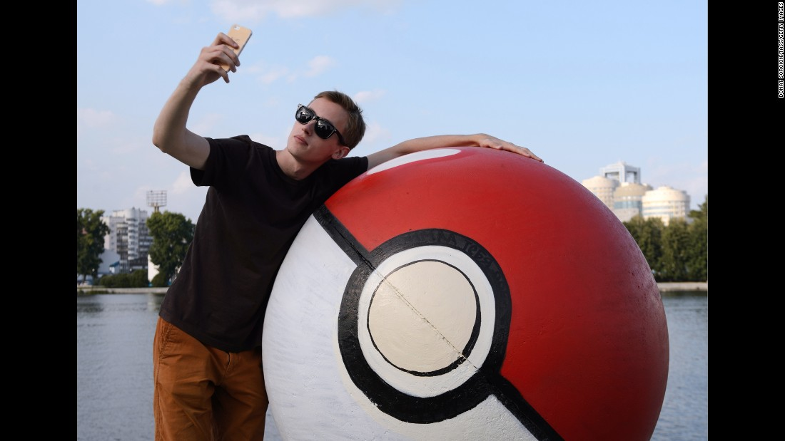 "A young man takes a selfie Tuesday, July 26, by a sphere monument that had been painted into a giant ""poke ball"" in Yekaterinburg, Russia. The mobile game ""Pokemon Go"" <a href=""http://money.cnn.com/2016/07/19/investing/pokemon-go-nintendo-shares/index.html"" target=""_blank"">has been a sensation</a> for its company, Nintendo."