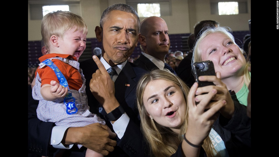 US President Barack Obama holds 10-month-old Brooks Breitwieser during a Hillary Clinton campaign event in Columbus, Ohio, on Tuesday, November 1.