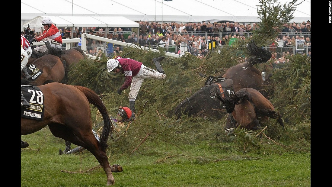 Horses and their jockeys fall over a fence Saturday, April 9, during the Grand National steeplechase in Liverpool, England.