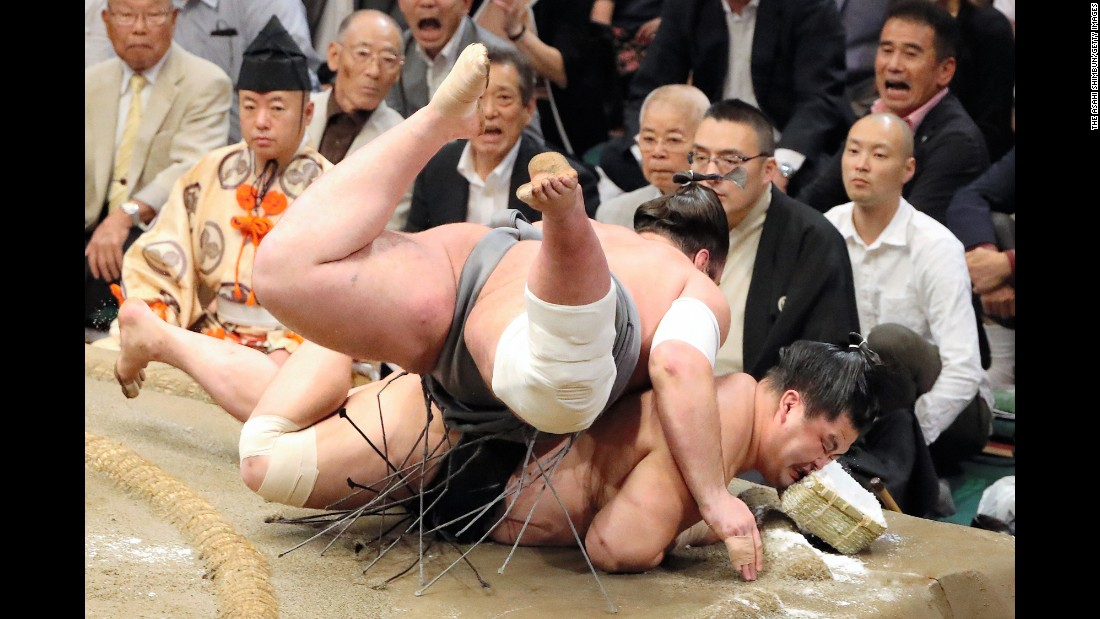 Tochinoshin, top, throws Myogiryu to win a match Friday, September 23, at the Grand Sumo Autumn Tournament in Tokyo.