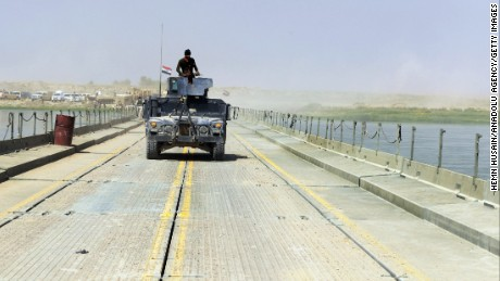 In this August file photo Iraqi security forces guard the temporarily constructed bridge that will be used to dispatch military deliveries on the Tigris River to Al Kayyarah town of Mosul, Iraq.