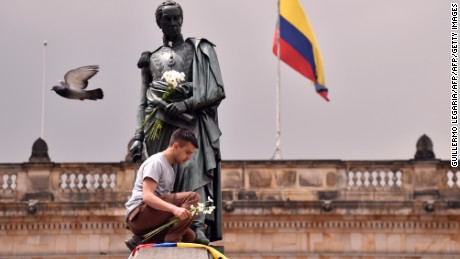 A colombian youngster places the national flag and a bunch of white flowers at the bottom of Simon Bolivar's monument to celebrate that Colombian president Juan Manuel Santos won the Nobel Peace Prize at Bolivar square 2016 on October 7, 2016, in Bogota.  Colombia's President Juan Manuel Santos dedicated his Nobel Peace Prize to the victims of his country's civil war, which he has worked to end through a contested peace accord with communist rebels. / AFP / GUILLERMO LEGARIA        (Photo credit should read GUILLERMO LEGARIA/AFP/Getty Images)