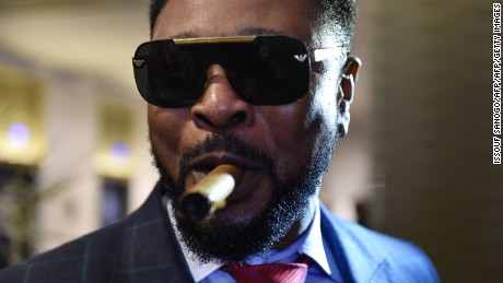 Ivory Coast's coupe-decale musician and member of Jet Sept Boro Sanguy smokes a cigar upon arriving to the Coupe-Decale Awards on October 15, 2016 in Abidjan.  Grand concert in Abidjan in the presence of all the stars of the genre, the first Coupe-Decale Awards took place on October 15, honoring a musical movement born in a decade of political and military crisis and a huge success. / AFP / ISSOUF SANOGO        (Photo credit should read ISSOUF SANOGO/AFP/Getty Images)