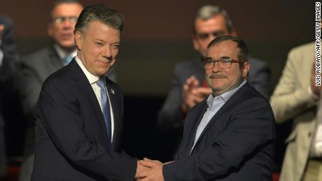 Colombian President Juan Manuel Santos, left, and the head of the FARC, Timoleon Jimenez, shake hands during the second signing of the historic peace agreement.