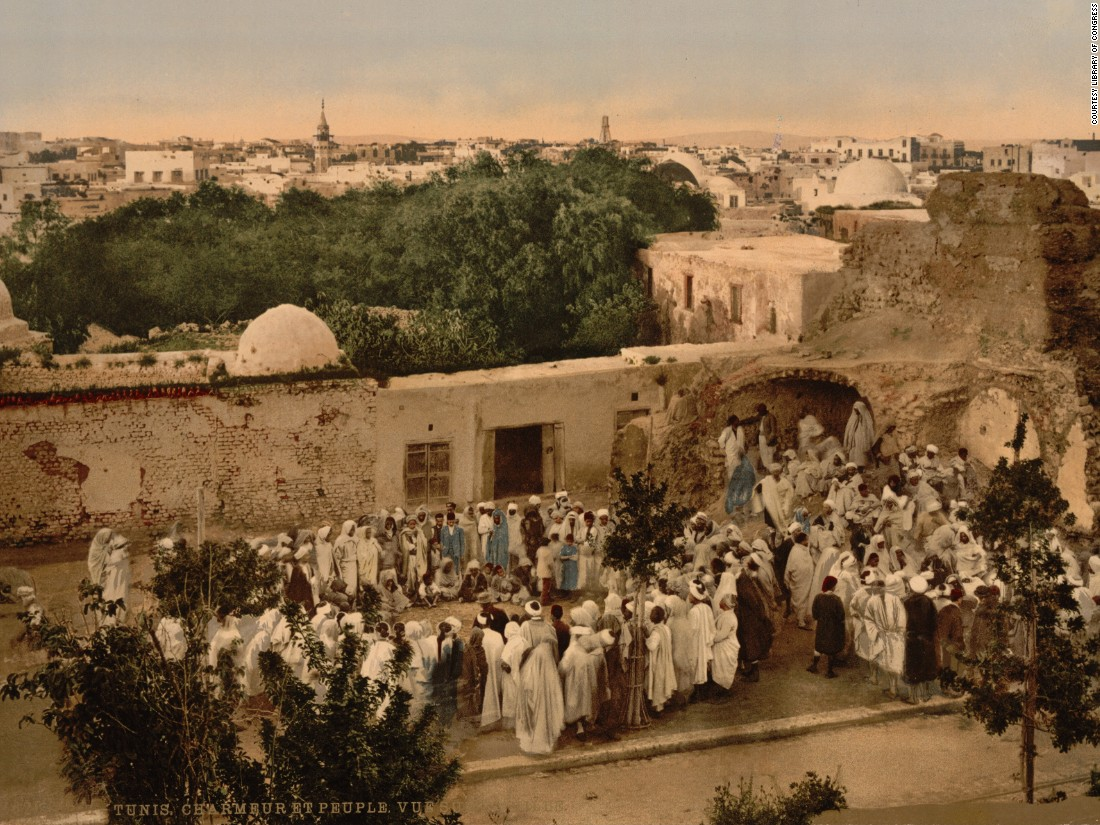 "A crowd surrounds a snake charmer in Tunis. Photochroms were created by taking the negative and exposing it to multiple flat surfaces such as stone, glass or zinc. As many as 24 separate slides would we be used, each printing a different color. Together the inks would blend and create realistic hues. (Find out more about the process <a href=""http://www.loc.gov/pictures/collection/pgz/process.html"" target=""_blank"">here</a>.)"