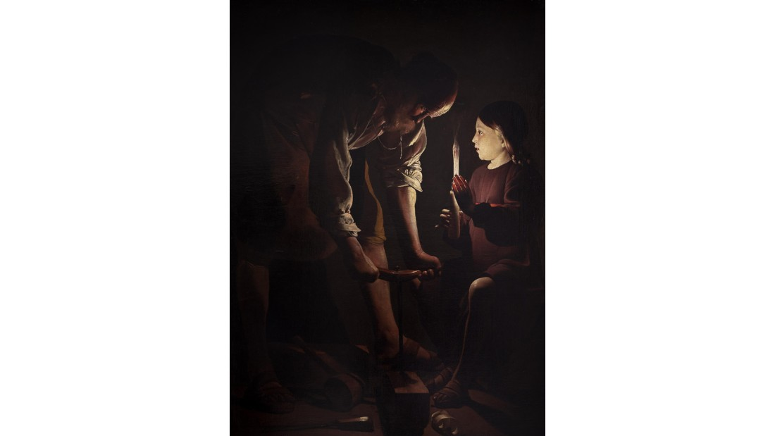 Here, eight-year-old Jesus Christ holds a candle for his stepfather, Joseph. The auger Joseph is using to drill a piece of wood creates the shape of the cross, referencing Jesus' future crucifixion.