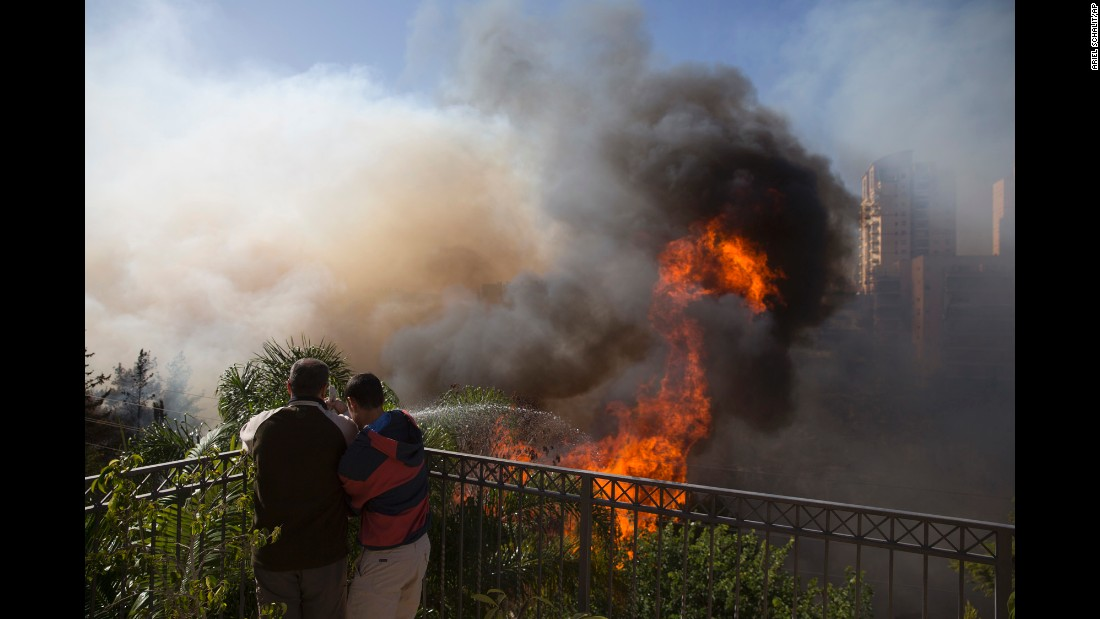 Haifa residents fight a wildfire with a hose on Thursday, November 24.