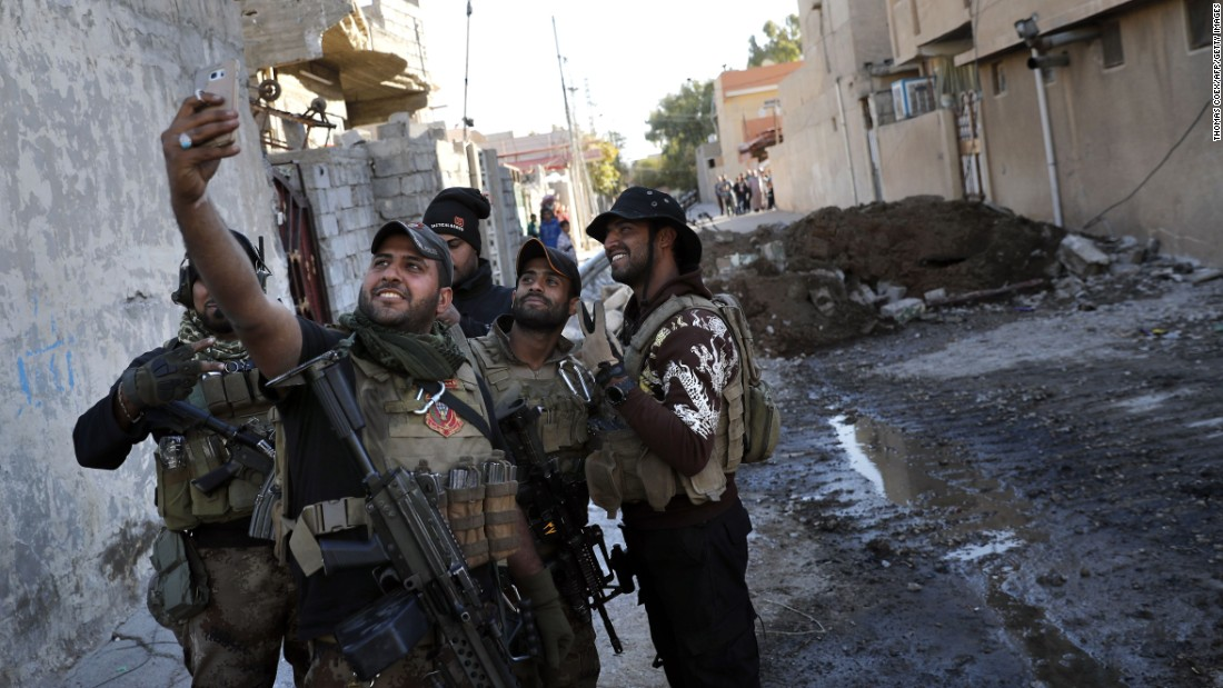 Iraqi soldiers take a selfie on a Mosul street after retaking the area from ISIS on Tuesday, November 22. Iraq is leading a coalition that also includes American and Kurdish troops.