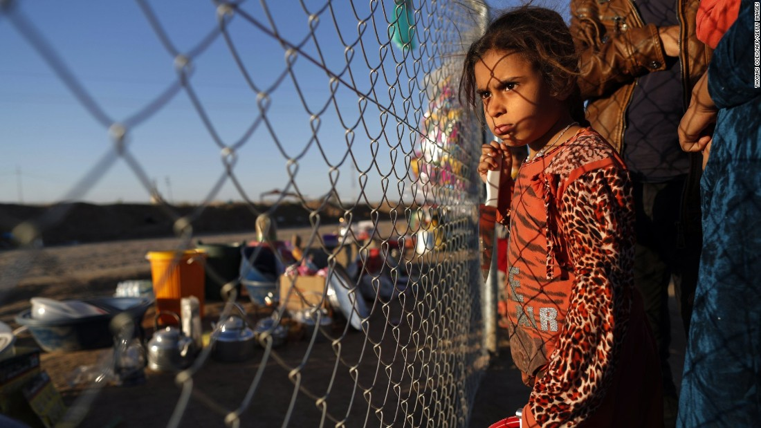 An Iraqi girl waits with her parents to buy food behind the fence of the Khazir refugee camp on Monday, November 21.