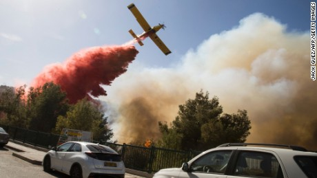 An Israeli firefighter plane helps extinguish a bushfire in the northern Israeli port city of Haifa on November 24, 2016.