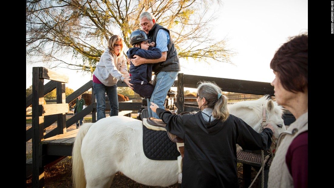 Harry Swimmer helps place John, 13, on his horse for a group riding class, with help from his mother, Joy Simon and Jenny Tsering.