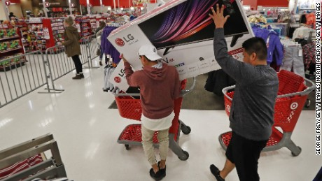 "OREM, UT - NOVEMBER 24: Shoppers  put a television into a basket that was part of ""Black Friday"" deals at a Target on November 24, 2016 in Orem, Utah. Retailers kicked off the unofficial start of the holiday season with sales that in many instances began on the Thanksgiving holiday.  (Photo by George Frey/Getty Images)"