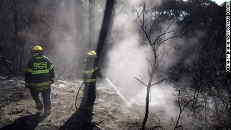 Israeli firefighters extinguish a fire in the northern Israeli city of Haifa following a wildfire, on November 25. Tens of thousands of Israelis fled raging bush fires that burned in the northern city of Haifa.