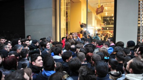 People wait outside of a department store for it to open in Thessalonik, Greecei on 25 November, 2016.  Long queues snaked outside department stores and roads were blocked near malls thousands of Greeks bucked falling wages and joblessness to join the country's first-ever Black Friday shopping craze. In Athens, Thessaloniki and other major Greek cities, the queues formed before participating stores -- mostly tech and clothes chains-- opened at 0600 GMT. It was soon clear that most of the shoppers were youngsters skipping school to take advantage of up to 80-percent reductions in the sales.