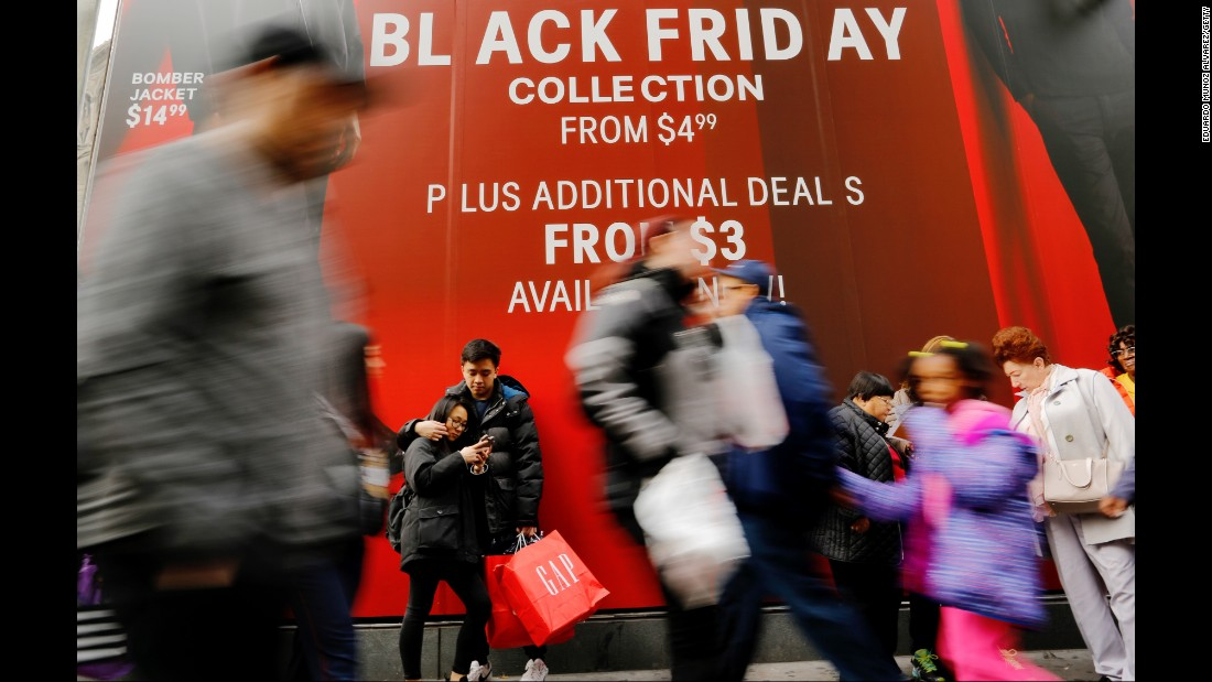 Shoppers walk next to retail stores in New York.