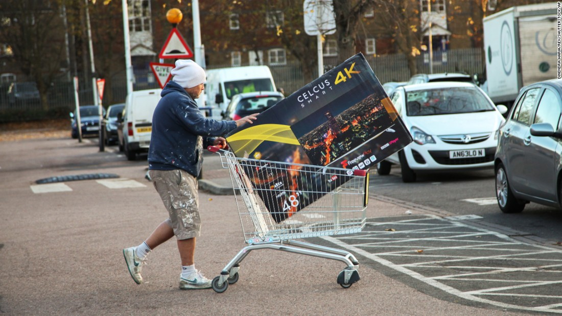 A man pushes a TV in a shopping cart outside a store in London.