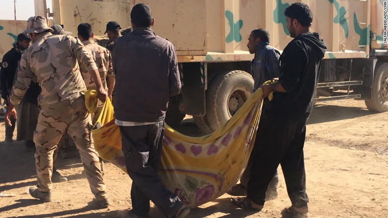 The bodies of civilians are loaded onto a truck for transfer to burial sites.