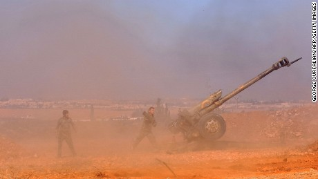 Syrian pro-government fighters fire a Russian 122mm howitzer gun as they advance in the recently recaptured village of Joubah during an offensive towards the area of Al-Bab in Aleppo province, on November 25, 2016. The Syrian army advanced in Aleppo, pounding the rebel-held east with strikes that killed dozens and added to the despair for more than 250,000 civilians under siege.