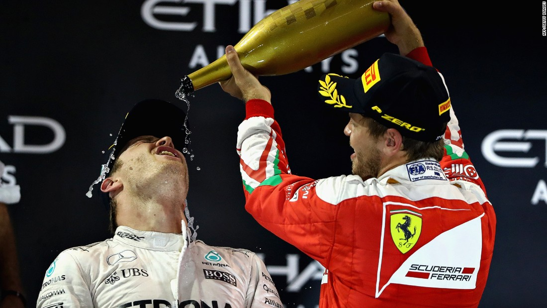 Rosberg is showered with champagne by his compatriot Sebastian Vettel, who was third for Ferrari.