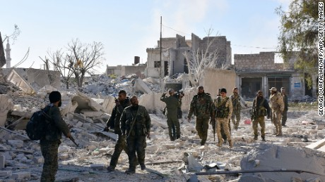 Syrian pro-government forces inspect an area on November 27, 2016 in the Masaken Hanano district in eastern Aleppo, a day after they resized it from rebel fighters. Syria regime forces seized two new rebel-held districts in Aleppo a day after they retook the largest opposition-controlled neighbourhood in the second city, a monitor said. The capture of Masaken Hanano -- which had been the biggest rebel-held district of Aleppo -- was a major breakthrough in a 13-day regime offensive to retake the entire city. / AFP / GEORGE OURFALIAN        (Photo credit should read GEORGE OURFALIAN/AFP/Getty Images)