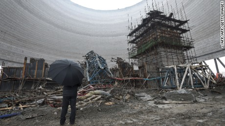 A man looks at the remains of a collapsed platform in a cooling tower at the plant in Fengcheng city, November 25, 2016.