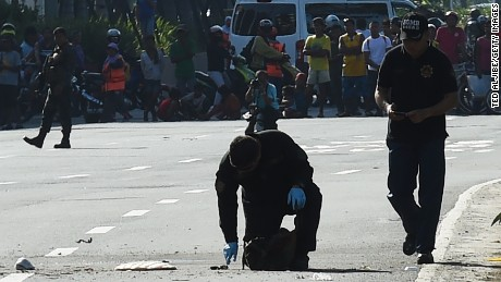 Members of police bomb disposal unit inspect the suspicious package after detonation using a water bomb supresor, along Roxas boulevard near the US embassy in Manila on November 28, 2016.  According to press reports quoting the police, the suspicious package was found inside a box along a with a cell phone and another electronic device, which the police successfully detonated. / AFP / TED ALJIBE        (Photo credit should read TED ALJIBE/AFP/Getty Images)
