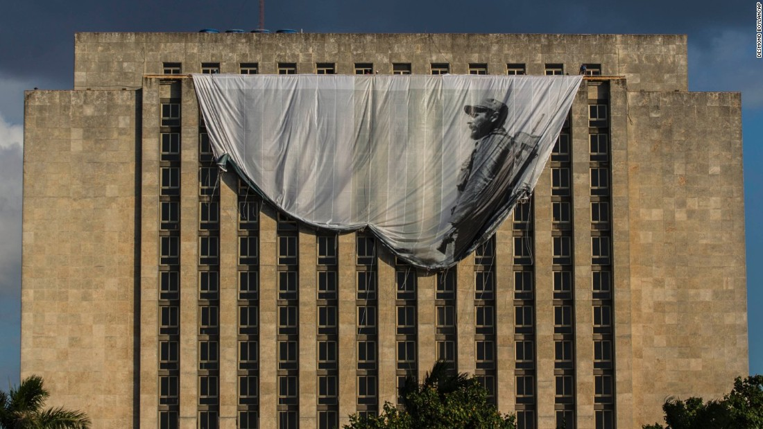 Workers hang a giant banner of a young Castro from the Cuban National Library in Havana on Sunday, November 27.