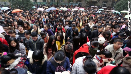 This picture taken on November 24, 2013 shows a group of candidates arriving for China's national civil service exam in a university in Nanjing, east China's Jiangsu province. More than one million people took China's national civil service exam on November 24, officials said, but faced huge odds against clinching one of the few government jobs available.               CHINA OUT     AFP PHOTO        (Photo credit should read STR/AFP/Getty Images)