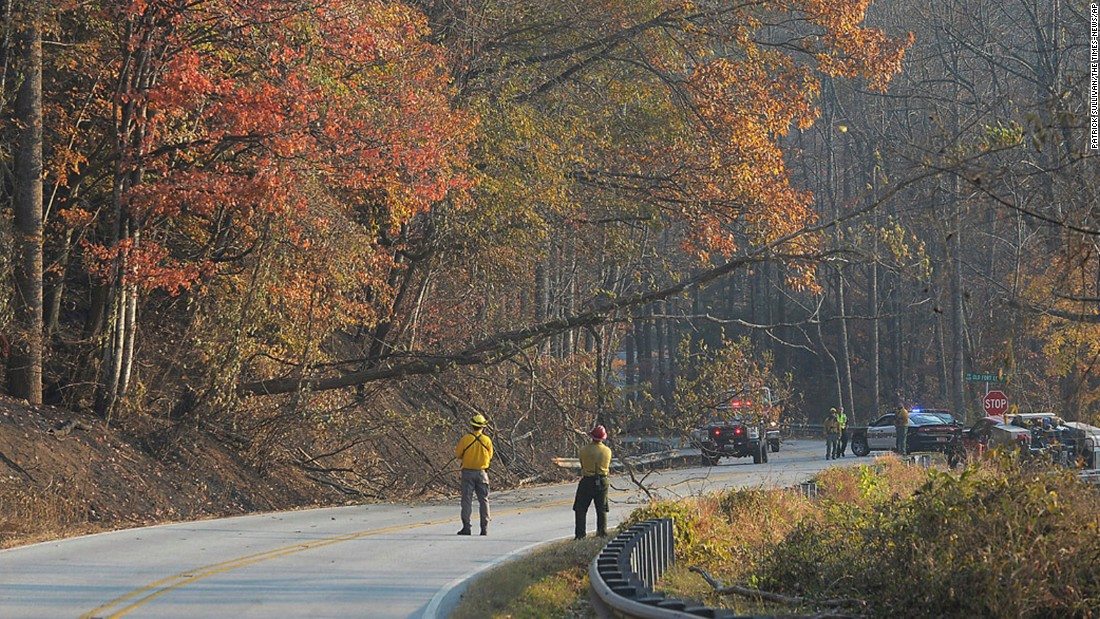 Fire crews bring down a dead tree along Highway 9 near the community of Bat Cave, North Carolina, on Friday, November 18.