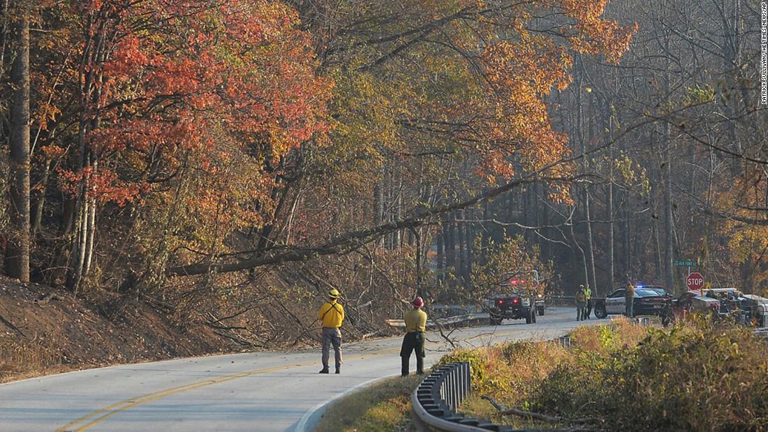 Fire crews bring down a dead tree along Highway 9 near the community of Bat Cave, North Carolina, on Friday, November 18.