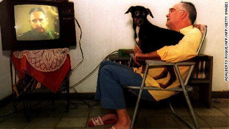 "HAVANA, CUBA:  An unidentified Cuban man sites with his dog and watches 01 January 1994 a speech by Cuban President Fidel Castro on television. Castro delivered the speech from Santiago de Cuba, which is approximately 560 miles east of Havana, and said during the speech that the current difficulties facing Cubans are ""small"" and that they can be conquered with ease. (Photo credit should read ADALBERTO ROQUE/AFP/Getty Images)"