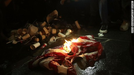 NEW YORK, NY - NOVEMBER 9: Protestors burn an American flag on Fifth Avenue outside of Trump Tower, November 9, 2016 in New York City. Republican candidate Donald Trump won the 2016 presidential election in the early hours of the morning in a widely unforeseen upset.