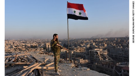 A pro-government soldier looks over the city of Aleppo on Monday.