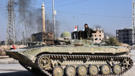 A member of Syrian pro-government forces drives a tank in the Haydariya northeastern neighbourhood in Aleppo on November 28, 2016, after they took control of the area from rebel fighters as part of their assault to retake the entire northern city.  In a major breakthrough in the push to retake the whole city, regime forces captured six rebel-held districts of eastern Aleppo over the weekend, including Masaken Hanano, the biggest of those in eastern Aleppo. The army captured the Sakhur, Haydariya and Sheikh Khodr neighbourhoods on November 28, 2016 while Kurdish forces took the Sheikh Fares district from rebels, the Syrian Observatory for Human Rights said.  / AFP / GEORGE OURFALIAN        (Photo credit should read GEORGE OURFALIAN/AFP/Getty Images)