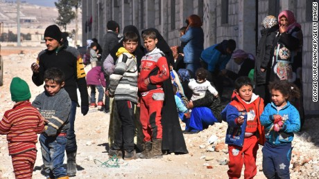 Syrian displaced families gather at a makeshift camp on November 27, 2016 in the government-held district of Jibreen in Aleppo, as civilians have fled the eastern part of the city in the past 24 hours as regime forces advance against rebel-held districts. / AFP / GEORGE OURFALIAN        (Photo credit should read GEORGE OURFALIAN/AFP/Getty Images)