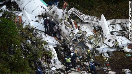 Rescuers search the wreckage of the charter plane Tuesday in mountains outside Medellin, Columbia.