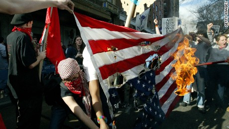 Anti-war protesters burn the American flag during a demonstration at Washington Square Park March 22, 2003 in New York City.